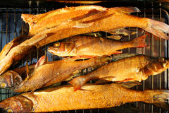 Fishes on smoking grill Stock Photo