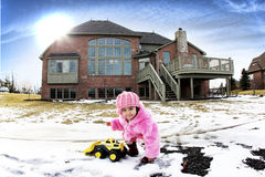 Fisheye. A two year old playing with her truck in the snow in the backyard Stock Photography