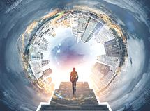 Fisheye cityscape panorama, man on stairs. Fisheye cityscape with a cloudy sky in the center. Bright sun is shining. Businessman ascending the stairs. Toned royalty free stock photo