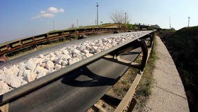 Fisheye of a conveyor belt transporting stones stock video footage