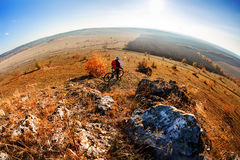 Fisheye of cyclist standing with mountain bike at sunrise against bright sun and blue sky. Stock Images
