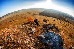 Fisheye of cyclist standing with mountain bike at sunrise against bright sun and blue sky. Royalty Free Stock Photos