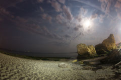 Fisheye - Night seascape with the moon and moving clouds Royalty Free Stock Photos