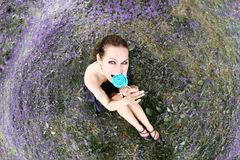 Fisheye portrait of beautiful woman with lollipop candy sitting on meadow Royalty Free Stock Image