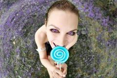 Fisheye portrait of beautiful woman with lollipop candy sitting on meadow Stock Photography