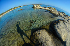 Fisheye seascape 4. Seascape fisheye view with a huge stones and shadow of photographer in morning sunlight, Carydi beach, Chalkidiki, Sithonia, Greece Royalty Free Stock Photos
