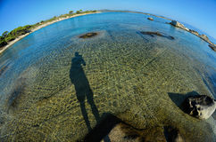 Fisheye seascape 5. Seascape fisheye view with a huge stones and shadow of photographer in morning sunlight, Carydi beach, Chalkidiki, Sithonia, Greece Royalty Free Stock Images
