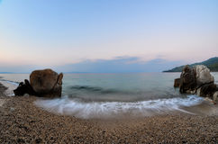 Fisheye seascape 9. Seascape fisheye view in late evening with sand, pebbles and milky waves, Fava beach, Chalkidiki, Sithonia, Greece Royalty Free Stock Photos