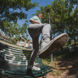 Fisheye shot of short hair girl standing on a bench Royalty Free Stock Image