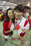 Fisheye shot of two female with SG50 tattoo on faces, hold mini national flags with pride and joy. SINGAPORE - AUGUST 8 : Fisheye shot of two female with SG50 stock photos