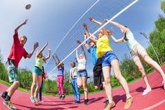 Fisheye sikt av tonår som spelar volleyboll på jordning Arkivbild