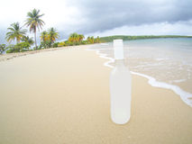 Fisheye of unknown bottle of liquor on the beach Stock Photography