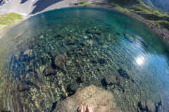 Fisheye view from above of alpine transparent lake and human feet into the water, in idyllic uncontaminated environment once cover Royalty Free Stock Photos