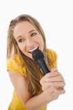 Fisheye view of blonde girl singing. With a microphone against a white background Stock Photos