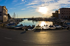 Fisheye view of boats, blue sky and sun reflection at Piran harbor, Istria Stock Photos