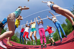 Fisheye view of children who play volleyball. On the game court outside during summer sunny day stock photo