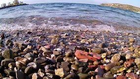 Gentle Sea water Lapping at Beach Pebbles, Greece. A fisheye view of gentle Gulf of Corinth sea water washing or lapping over small pebbles on beach, Greece stock video footage