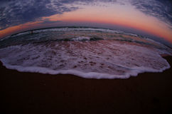 Fisheye view of sea waves at sunset Stock Photos