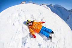 Fisheye view of smiling boy in mask laying on snow Stock Photography