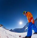 Fisheye view of smiling boy in ski mask skiing. On slope of beautiful mountain during sunny winter day on Krasnaya polyana, Sochi royalty free stock photo