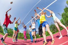 Fisheye view of teens playing volleyball on ground. Fisheye view of teenagers playing volleyball on the playground outside during summer sunny day stock photography