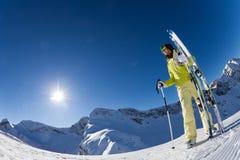 Fisheye view of woman holding ski with poles. Fisheye view of woman standing and holding ski and ski poles during sunny winter day on Krasnaya polyana ski resort Royalty Free Stock Photos