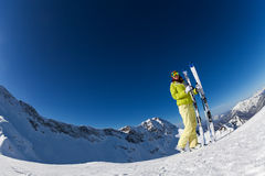 Fisheye view of young woman in mask holding ski. Fisheye view of young woman in mask standing and holding ski and ski poles during sunny winter day on Krasnaya Royalty Free Stock Photo