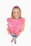 Fisheye view of a young woman tending a piggy-bank Royalty Free Stock Images
