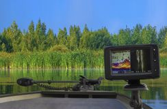 Fishfinder, echolot, fishing sonar at the boat. On natural green shore background stock photos