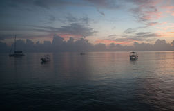 Fishier Boats during Sunrise in the sea. Stock Photo