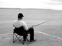 Fishing. Fisherman fishing off the end of the pier Royalty Free Stock Photography