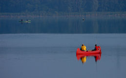 Fishing 1. Father and son fishing on a lake in a red canoe Stock Photos