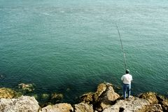 Fishing. Men fishing by the ocean Royalty Free Stock Photos