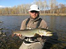 Fishing. (Fisherman catched taimen in Mongolian river Royalty Free Stock Photo