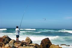 Fishing. The fisherman with a fishing tackle on coast of Atlantic ocean in hot day Stock Photos