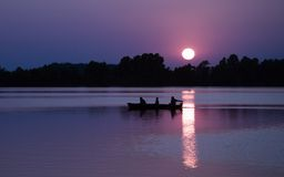 Fishing. People in a boat fishing at sunset Royalty Free Stock Photography