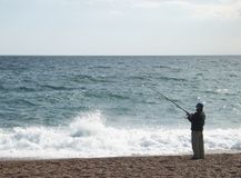 Fishing. On pebble beach Royalty Free Stock Image