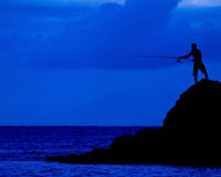 Fishing. The dark figure of a man fishing from a rock into the sea Stock Photo