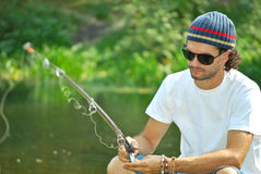 Fishing. Handsome man with sunglasses and sunhat fishing from a pier on a sunny day Royalty Free Stock Image