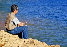 Fishing. Man Fishing On Rocky Shore Stock Photo