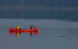 Fishing 2. Father and son fishing on a lake in a red canoe Stock Image