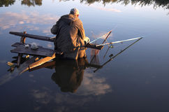 Fishing. Man fishing in river with reflexion of sky Stock Photos
