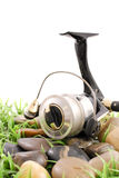 Fishing. Reel on Rocks and Grass royalty free stock photo