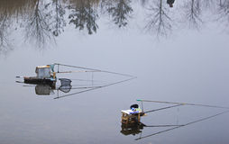 Fishing. Two fishing guys were having their breakfast at the riverside, leaving their poles in position Stock Photos