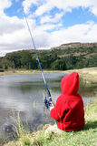 Fishing. Child fishing on the edge of a pond royalty free stock image