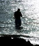 Fishing. This is a silhoette of a man fishing at sunset in the ocean Royalty Free Stock Photos