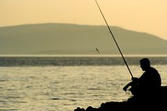 Fishing. A man fishing in the ocean, dawn Royalty Free Stock Photo