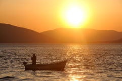 Fishing. A single angler enjoys fishing from a boat on a beautiful sunset royalty free stock photography