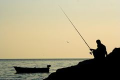 Fishing. A man fishing in the ocean, dawn Royalty Free Stock Photography