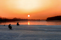 On fishing. Two fishermen fish in the evening on a sunset Royalty Free Stock Images